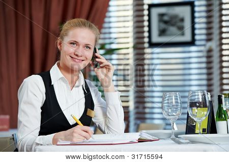 Happy beautiful restaurant manager woman administrator at work place with phone