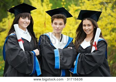 group of three smiling graduate students in spring park after finishing education with diploma