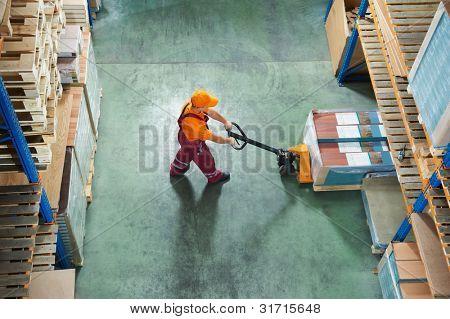 trabajador con horquilla carro apilador en almacén carga de paneles de muebles