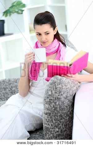 Woman sitting in the sofa reading a book and drinking coffee or tea