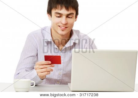 A businessman with a credit card, laptop sitting at the desk , isolated on white background