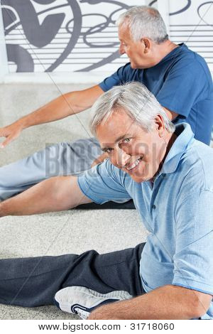 Senior men stretching in fitness center before exercising