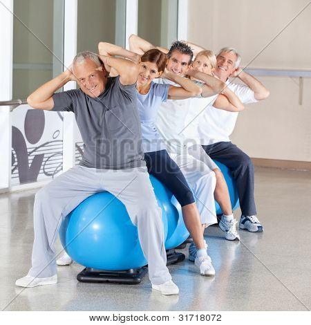 Happy senior citizens doing back exercises on gym ball in fitness center