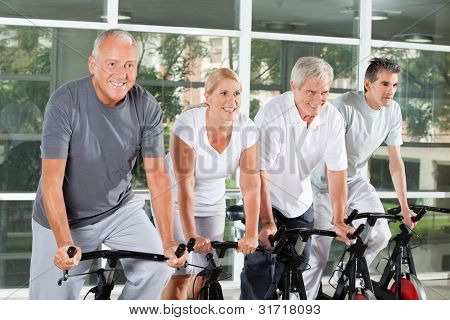 Happy senior people riding bikes together in fitness center