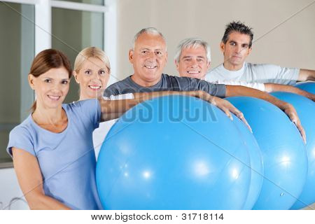 Happy senior citizens holding blue gym balls in fitness center
