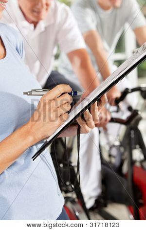 Fitness trainer with checklist on clipboard in gym