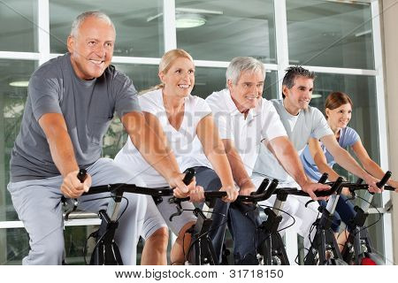 Happy senior citizens exercising in spinning class in fitness center