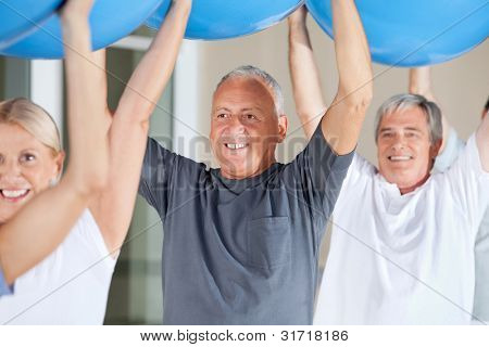 Senior citizens exercising with blue gym balls in fitness center