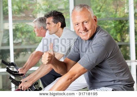 Happy senior Man auf Fahrrad Daumen halten, im Fitness-center