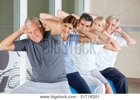 Happy senior people doing back exercises in gym