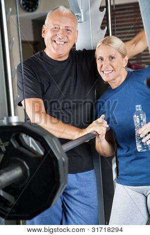 Happy smiling senior couple exercising in fitness center
