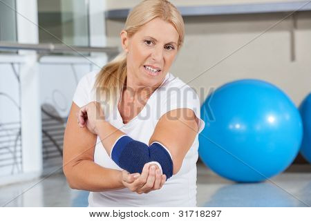 Elderly woman holding her aching elbow with bandage in gym