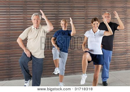 Happy seniors doing aerobic exercises in gym
