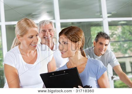 Female fitness trainer talking to senior woman in gym
