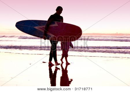 weibliche Surfer und ihre Tochter zu Fuß am Strand in den Sonnenuntergang