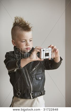 Portrait of boy with mohawk in leather jacket taking picture of himself