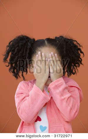 Portrait of Asian girl with ponytails with hands over her face