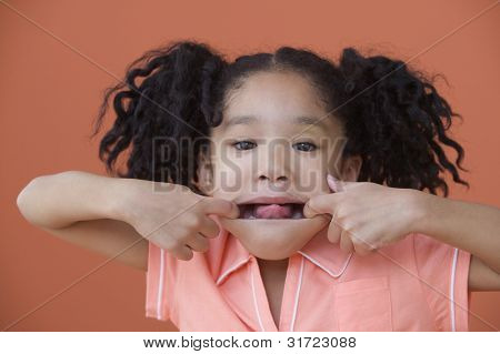 Portrait of Asian girl with ponytails posing with stretched out mouth