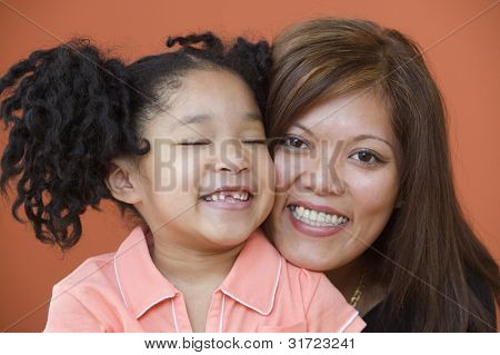 Portrait of mother holding young daughter with eyes closed