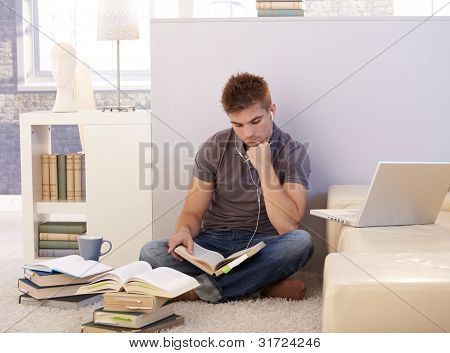 College student boy studying at home surrounded by books, notes, listening to music via headphones, sitting on living room floor.