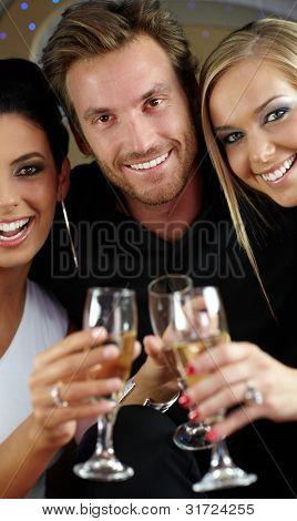 Hermosas jóvenes beber champagne, tintineo de vasos, sonriendo alegremente.