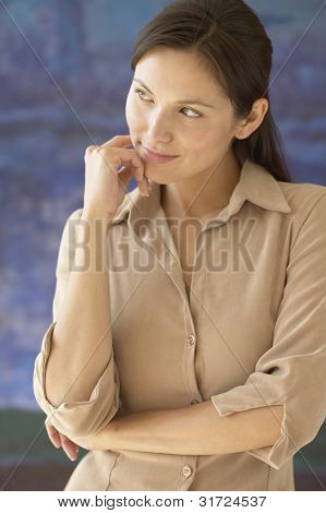 Woman standing with hand on chin looking sideways