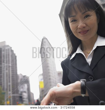 Businesswoman smiling with cityscape behind her