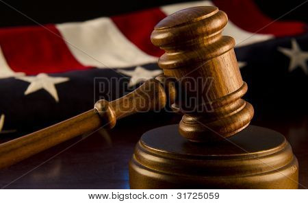 Wooden Judge's gavel with American flag in background.
