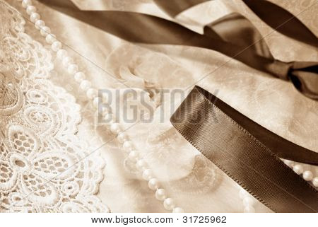Wedding montage in sepia tones.  Photos blended together include macros of elegant lace, pearls, satin fabric, floral bouquet and satin ribbon.