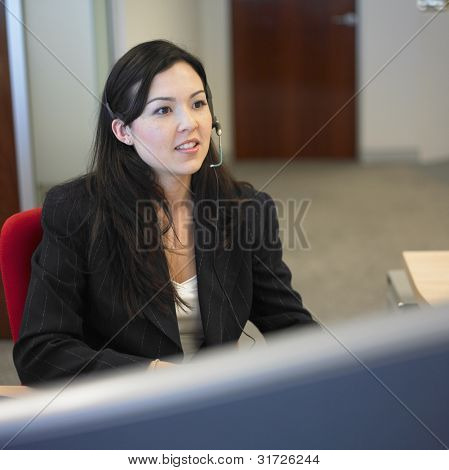 Woman sitting in office wearing earpiece