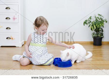 Linda Niña alimentando un gato blanco