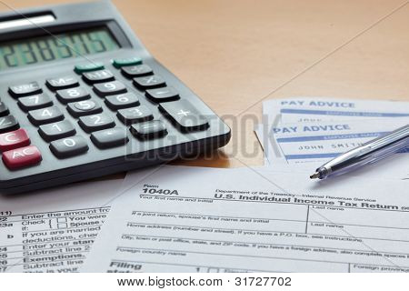 Photo of a blank 1040 tax form with payslips and calculator. The payslip is a mock up the names and all other information on it is fictional.