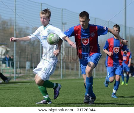 KAPOSVAR, HUNGARY - MARCH 17: Adam Hampuk (white) in action at the Hungarian National Championship under 18 game between Kaposvar (white) and Videoton (blue), March 17, 2012 in Kaposvar, Hungary.