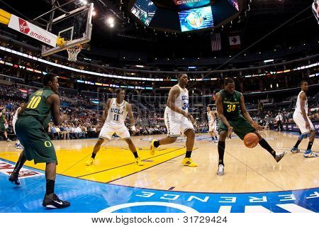 LOS ANGELES - MARCH 10: Oregon Ducks G Johnathan Loyd #10 inbounds the ball to Oregon Ducks F Joevan Catron #34 during the NCAA Pac-10 Tournament basketball game on March 10 2011 at Staples Center.