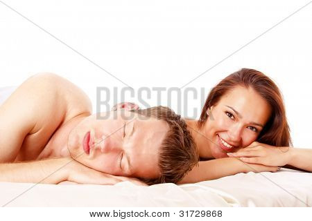 Attractive couple in bed . Young woman smiling at camera and young man sleeping