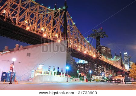 Roosevelt Island at night with Queensboro Bridge and New York City midtown Manhattan skyline.