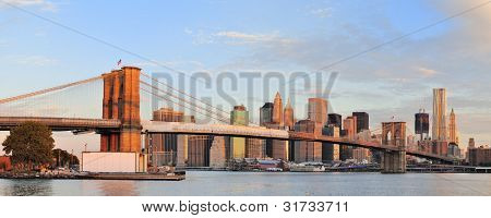 Brooklyn Bridge with lower Manhattan skyline panorama in the morning with colorful cloud over East River in New York City
