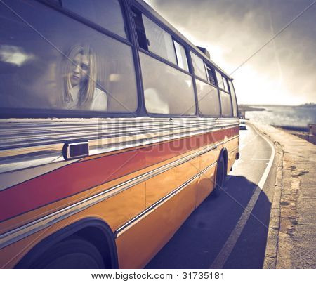 Young woman sitting in a coach bus [design of the bus modified]