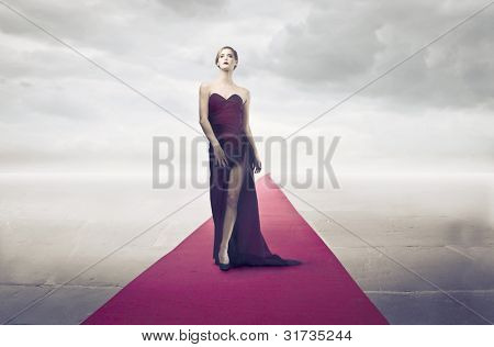 Beautiful elegant woman walking on the red carpet