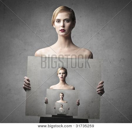Beautiful woman holding a picture of herself holding a picture of herself to infinite