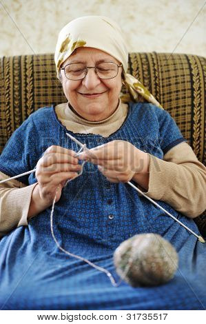 Image of an old arabic woman sitting on a sofa and knitting