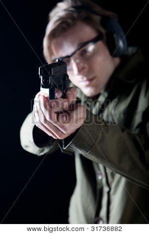 Mann mit dem Ziel, einer Waffe mit Schutzausrüstung