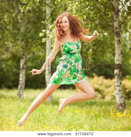 Young redhead woman jumping in the park with flowers