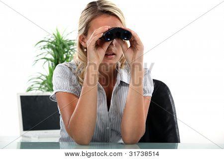 weibliche Büroangestellte mit Fernglas