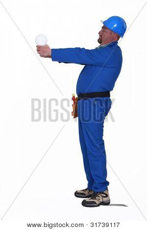Worker holding large light bulb