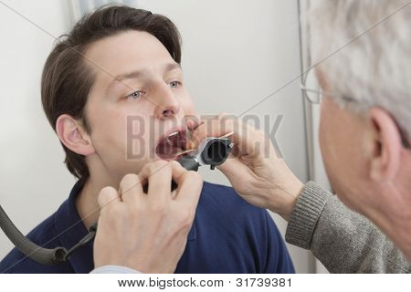 Young man getting his throat checked by male doctor at clinic