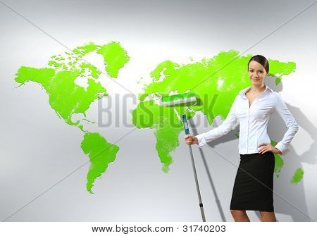 Businesswoman with paint brush and world map on the background