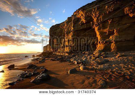 Golden sandstone cliff sunset at hive beach, Burton Bradstock near Bridport, Dorset.