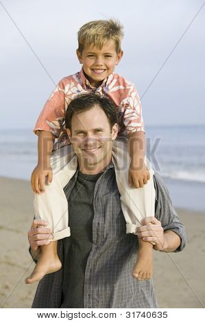 Portrait of boy on fathers shoulders at beach