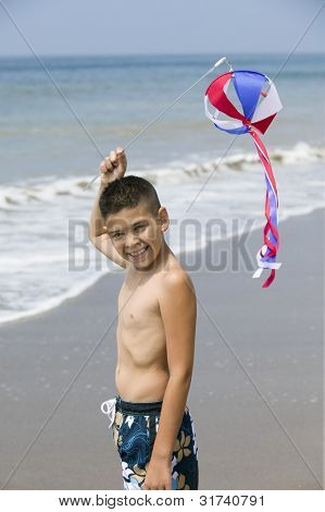 Portrait of boy with kite on beach